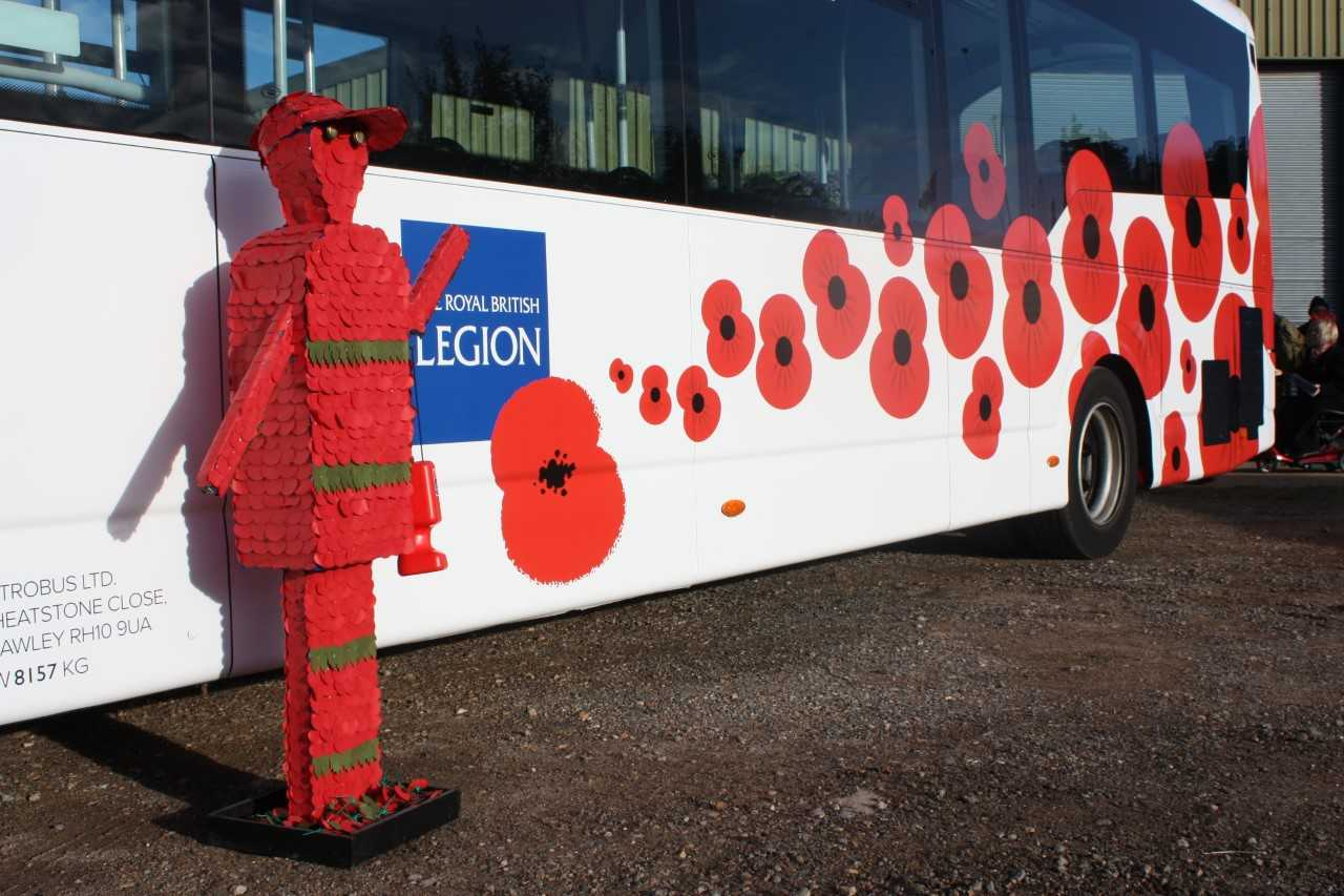 A photo of a bus decorated with the Royal British Legion logo and images of poppys