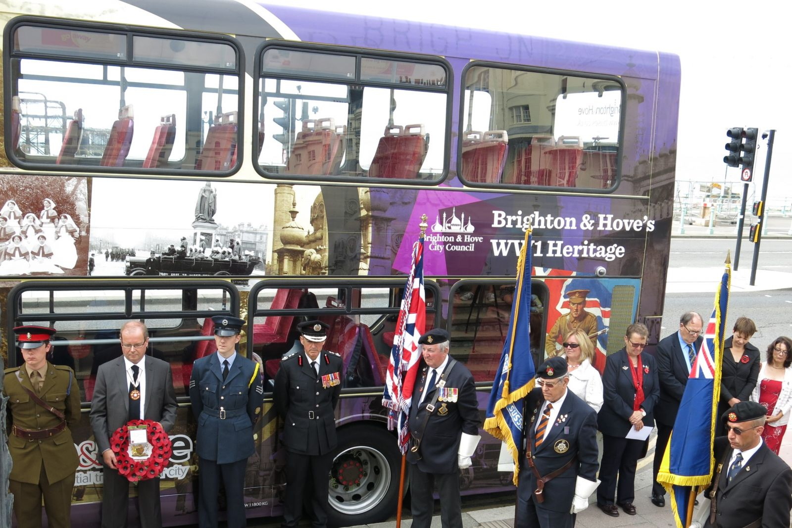 Photo of a bus decordated with photos of Brighton during WW1, a remebrance day parade stands in front of it